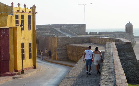 A couple take a stroll along the old city walls of Cartagena