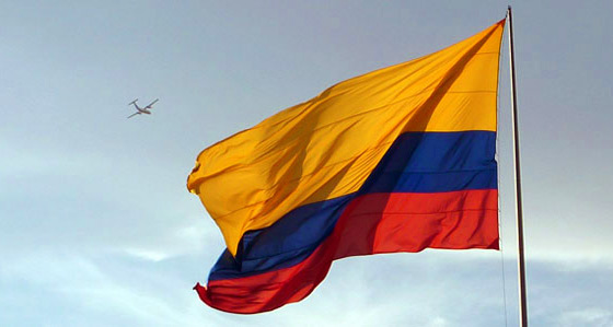 The Colombia flag with an airplane flying overhead