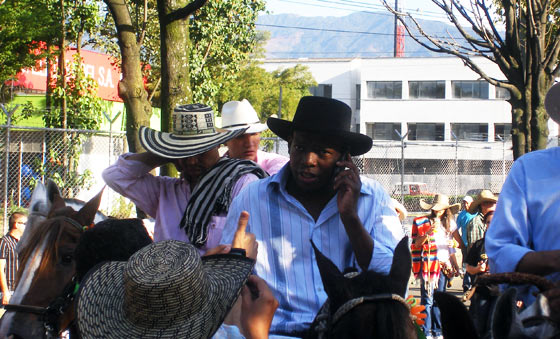 'El Tino' Asprilla takes a phone call during the Cabalgata in Medellin