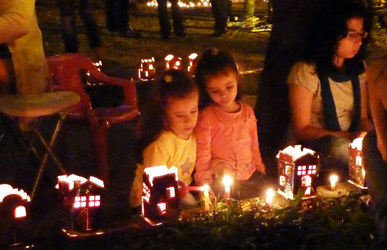 Young girls lighting candles in a park